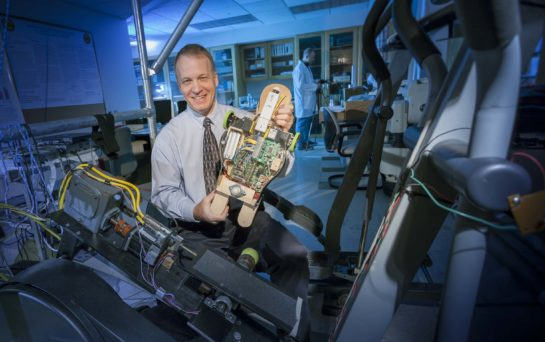 Alumnus Peter Pidcoe holds an early prototype of the Self-initiated Prone Progression Crawler.