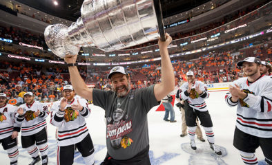 Alumnus Mike Gapski holds the Stanley Cup above his head while surrounded by Chicago Blackhawks hockey players