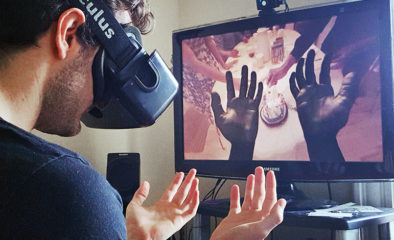A young white male is wearing a virtual reality headset and looking down at his hands. On the screen in front of him, his hands are projected and simulating a vision impairment