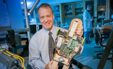 Alumnus Peter Pidcoe holds an early prototype of the Self-initiated Prone Progression Crawler