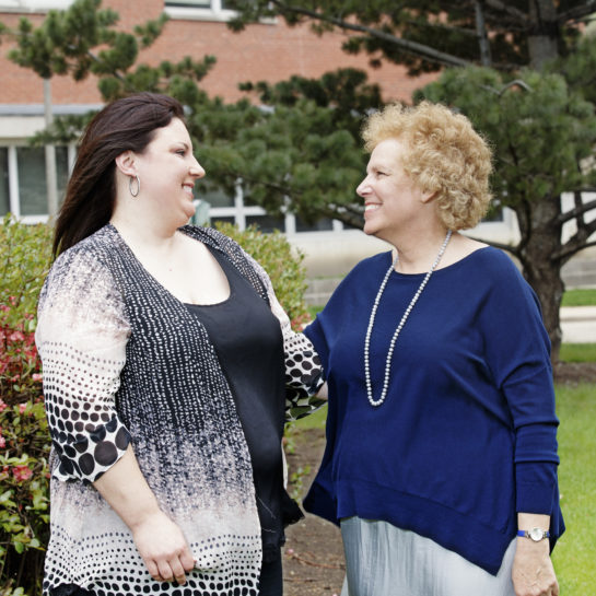 AnnaMaria Baraglia and Carol Gottlieb stand side-by-side outdoors