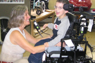 Foto de niño sonriente siendo evaluado para una silla de ruedas por su terapista