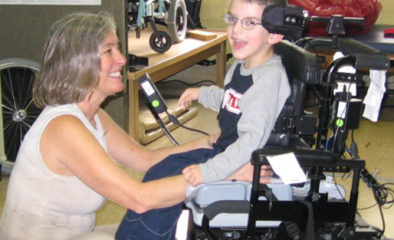 A woman and boy in a wheelchair smiling