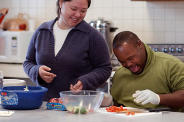 A woman and man preparing food in the kitchen