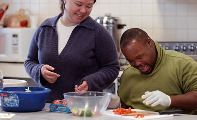 Woman helping African American man with disabilities how to work in kitchen