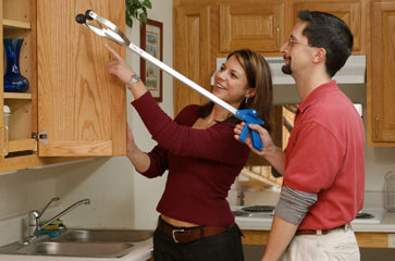 a woman with a man using a reach stick at a cabinet
