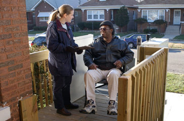 A woman talking with a man in a wheelchair by a ramp