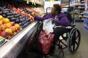 Foto de una mujer en silla de ruedas comprando frutas y vegetales en el supermercado
