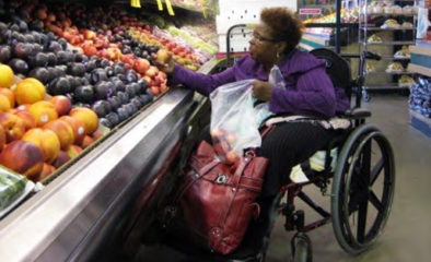 A woman in a wheelchair grocery shopping