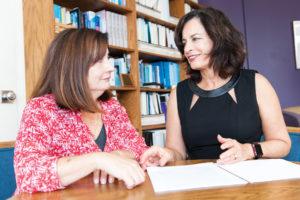 Sandy Magaña and Tamar Heller talking by a document