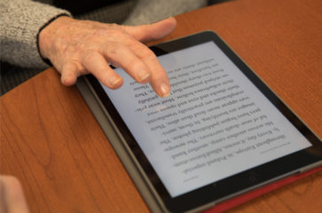 Elderly man's hand using an electronic tablet