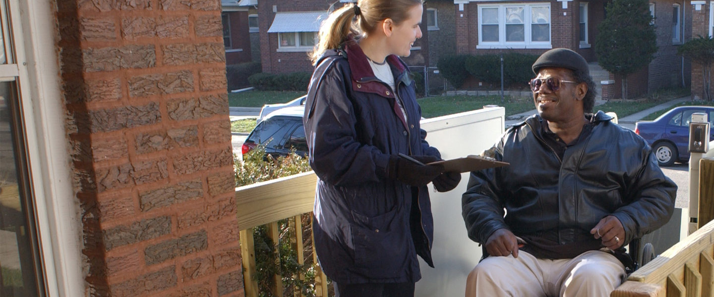 Woman holding a clipboard is speaking with a man on a wheelchair. They are both on a wooden wheelchair ramp.