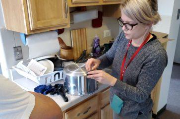 Therapist helps man use kitchen tools