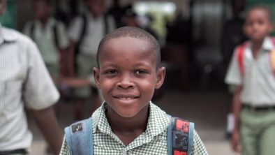 Smiling child with backpack in a school yard