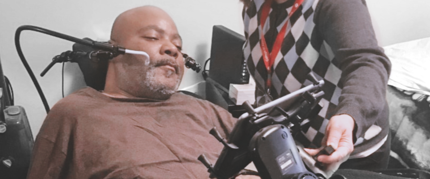 Man using multiple technology devices to access a tablet computer. A clinician is adjusting the tablet mount.