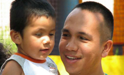 A latino man holding his young child and smiling