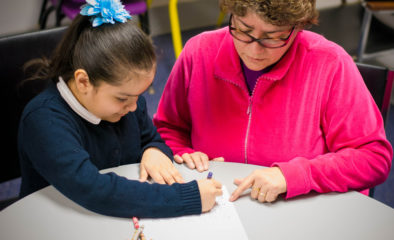 A woman helping a child work with pencil and paper