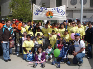 "Groupo SALTO group together outside holding a ""Grupo SALTO"" banner"