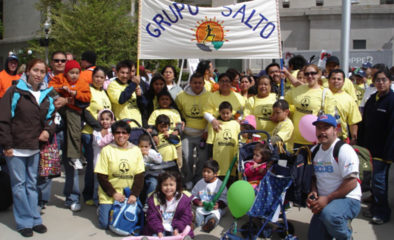 A group of families outside at a walk holding a Grupo SALTO banner