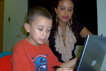 A mother helping her son learn on a computer screen