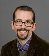 Brian Grossman, a white smiling man with glasses in his mid 30s, dressed in a purple plaid shirt, green sweater, and brown corduroy blazer.
