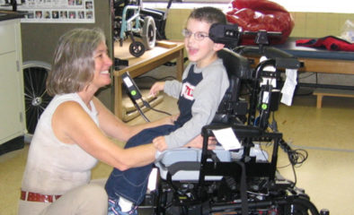 An ATU staff member helping a child in a wheelchair