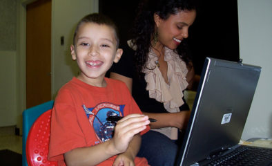 A child with disabilities working on a computer with a Family Clinics staff member