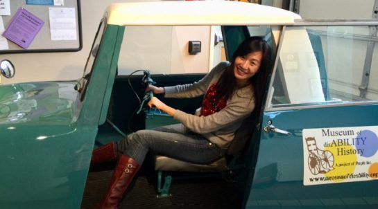 Sandie in a car at the Museum of DisABILITY History