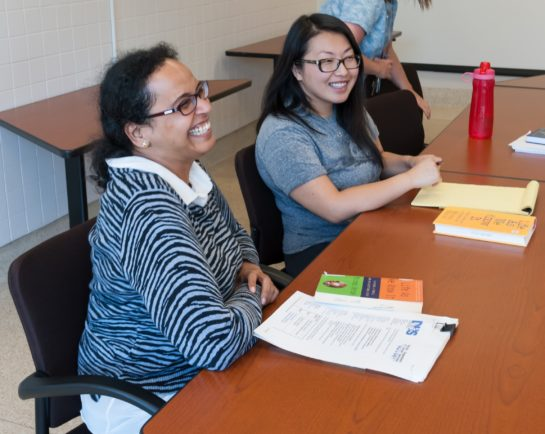 Two smiling students sitting at a classroom table