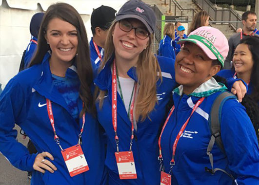 Three female LEND trainees at the Chicago Marathon. One is holding a prosthetic leg.