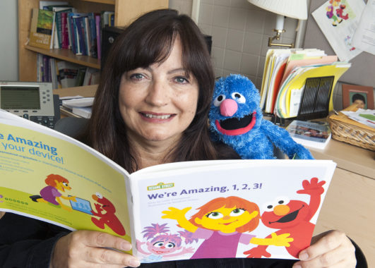Sandy Magana sits holding a children's book while a small, stuffed Cookie Monster looks over her shoulder