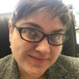 Photograph of a white woman with short brown hair and black glasses seated in her office at DHD
