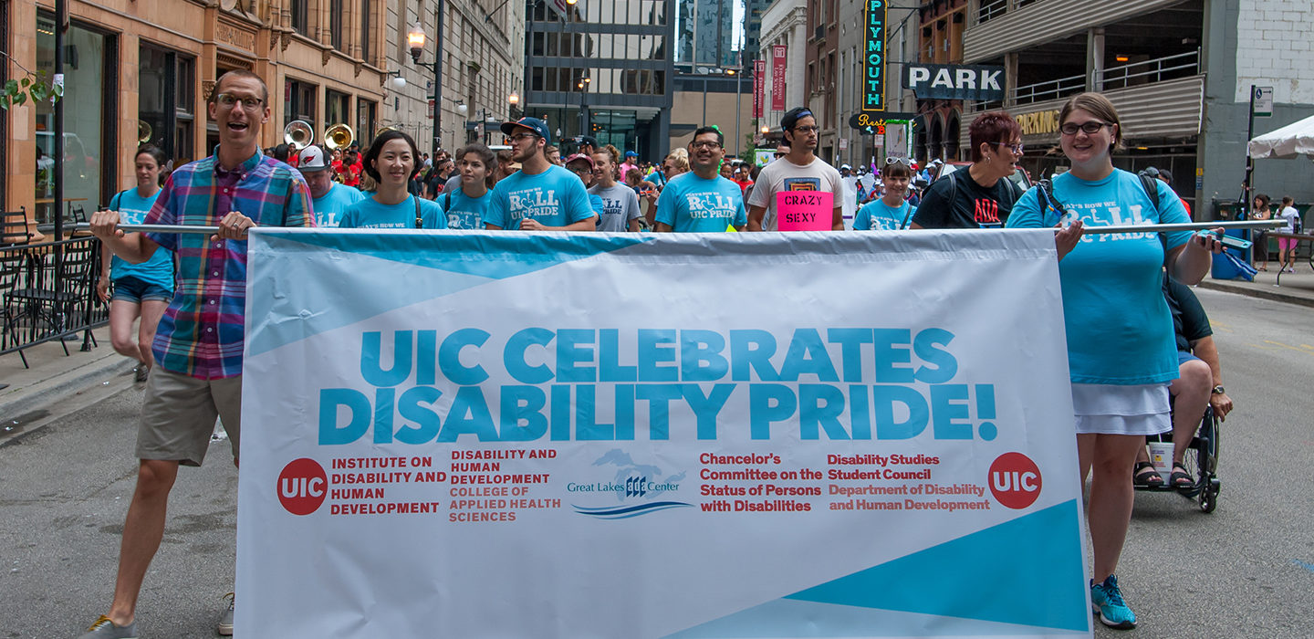 "DHD group at the Disability Pride Parade with a banner ""UIC Celebrates Disability Pride!"""