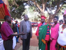 Patrick in his UIC red and blue cap and gown with a green fabric over it in Uganda standing next to his wife along with with 3 people at his village graduation celebration