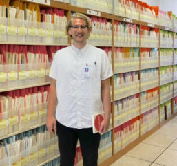 PhD student Drew standing in front of bookshelves of documents