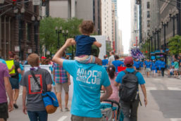 Man is walking with a toddler on his shoulders