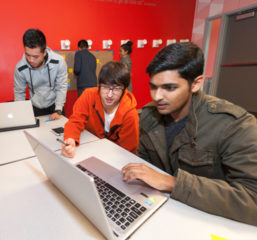 Two students look at a laptop screen and other students are studying in the background