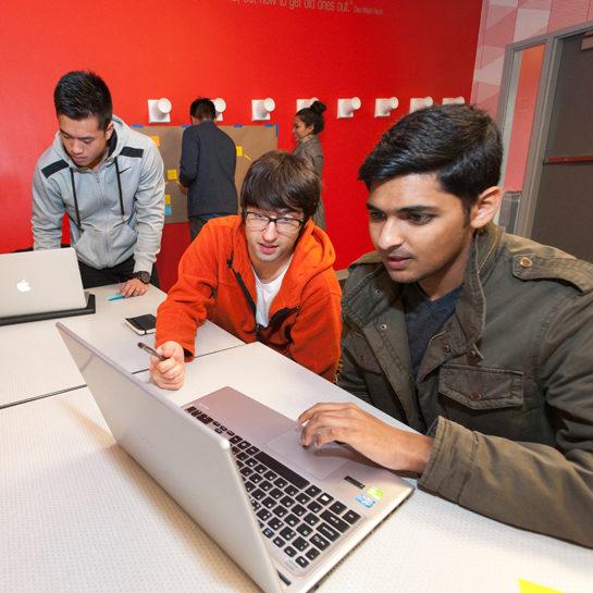 three men working on a laptop