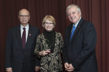 Three individuals stand in front of a red backdrop with woman in middle holding up an award