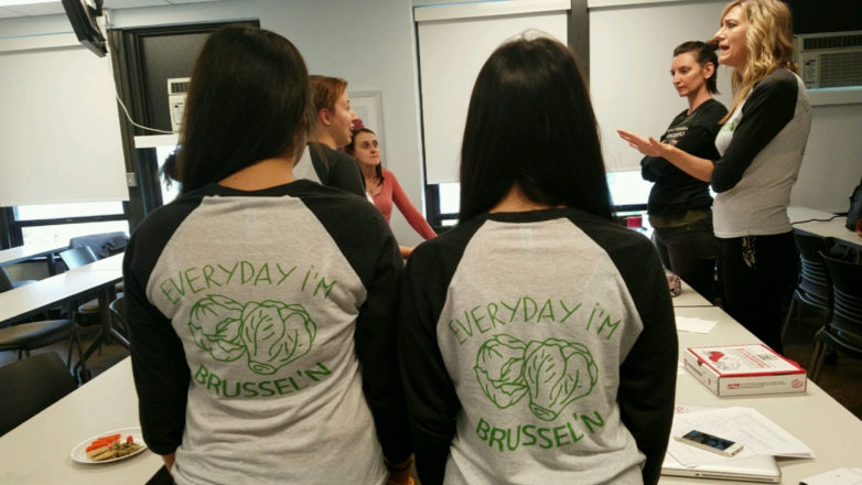 """Nutrition students Barbara Bilski and Sumar Kullab showing off their SNA t-shirts that say """"Everyday I'm brussel'n"""" with illustrations of brussel sprouts"""