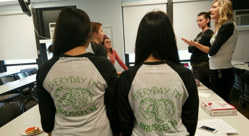 "Nutrition students Barbara Bilski and Sumar Kullab showing off their SNA t-shirts that say ""Everyday I'm brussel'n"" with illustrations of brussel sprouts"
