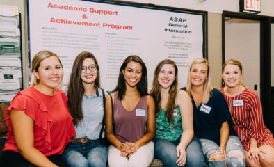 A group of six women sit in front of a bulletin board with ASAP information