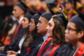 A group of students wearing cap and gowns sit looking forward