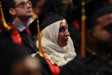 A student wearing a cap and gown is sitting down