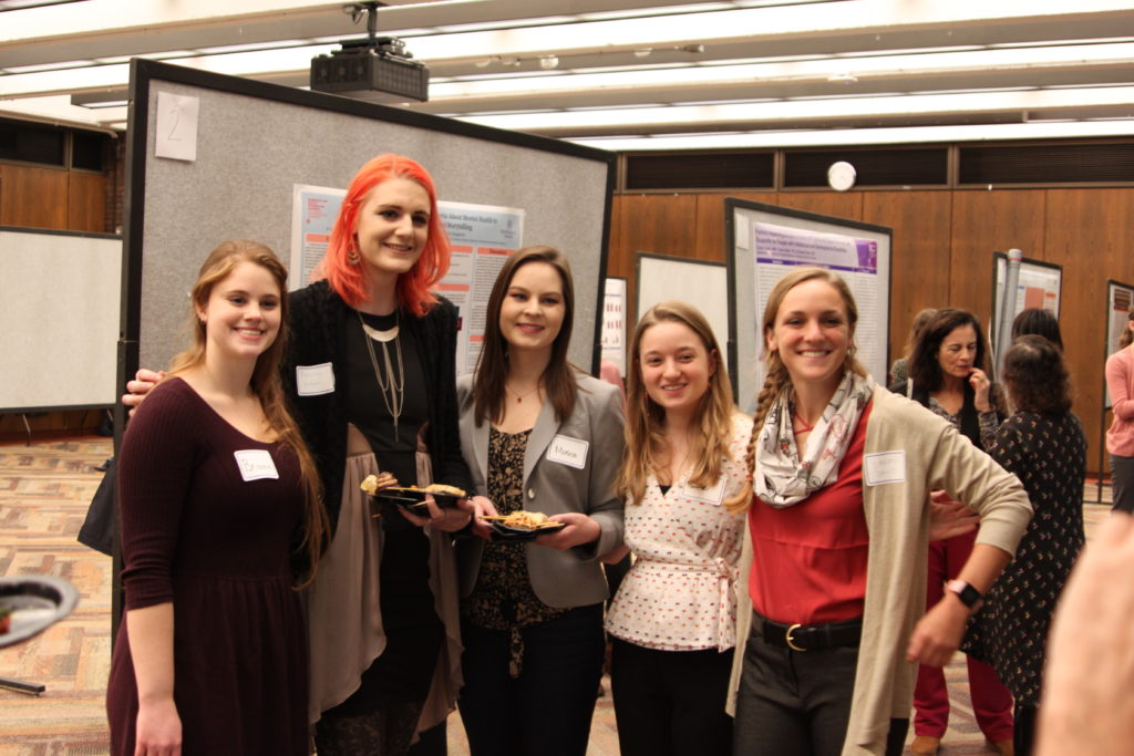 A group of five biomedical visualization students stand in the research poster presentation hall