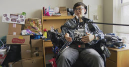 Noah Ohashi sits in a wheelchair in a college dorm room with a microphone in front of them