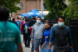 People wearing protective masks wait in line outside a Catholic Charities Brooklyn and Queens pop-up food pantry in the Brooklyn borough of New York on May 29.