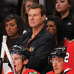 Mike Gapski looks forward as he stands behind sitting Chicago Blackhawks players