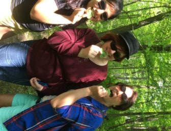 Three nutition students are eating freshly picked garlic mustard