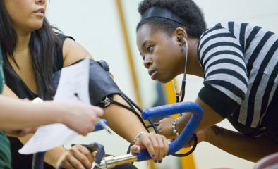 African American female student with stethescope check blood pressure of classmate on stationary bike